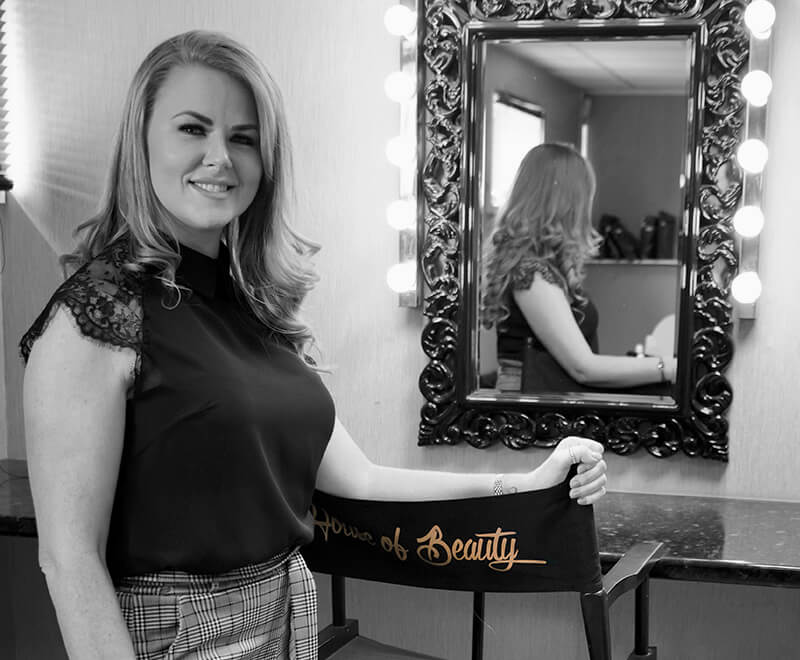 About Lindsey Easton - Black and White photograph of Lindsey posing at the side of a large mirror showing herself and her reflection